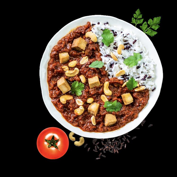 Tikka Masala verbindet man sofort mit Indien, aber wusstest du, dass das Gericht in einem indischen Restaurant in Großbritannien erfunden wurde und in Indien gar nicht bekannt ist? <b>Indischen Genuss</b> liefert unser Tikka Tofu Masala trotzdem, da die feinen Gewürze tief in der indischen Küche verwurzelt sind. Durch den Ersatz des typischen Hähnchens durch Tofu, ist dieses Tikka Masala <b>vegan</b>. Den in fein gewürfeltem Knoblauch, <b>frisch geriebenem Ingwer</b> und feinen indischen Gewürzen <b>marinierten Tofu</b> braten wir als erstes scharf an. Danach landet er in einem fruchtigen Tomatensugo, das dir abgeschmeckt mit Kurkuma, einer feinen Zimtnote, Cumin und Kardamom indischen Genuss liefert. Gehackter Koriander bringt eine schöne Frische ins Spiel, Erdnüsse und Cashews sorgen für <b>knackige Highlights</b>. Zu deinem Tikka Tofu Masala liefern wir dir entweder eine Portion duftenden Basmati-Mix oder leckere Udon Noodles.
