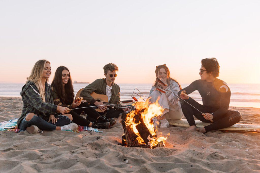 Achtsamkeit bedeutet Momente, wie zum Beispiel mit Freunden am Strand an einem Lagerfeuer zu sitzen, bewusst wahrzunehmen